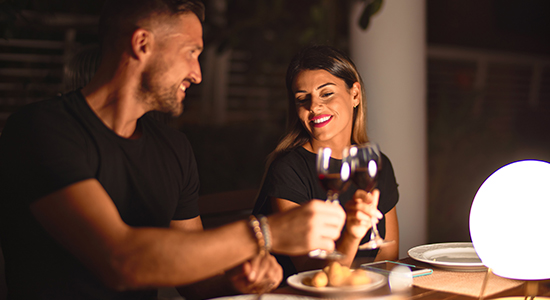 young beautiful couple dinning on celebration toasting and smiling at terrace